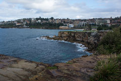 Rocky shoreline of Coogee beach. Cliff faces and waves surrounding Coogee Beach in Sydney, Australia Stock Photo