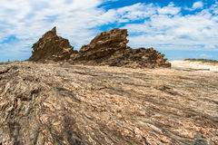 Rocky Shoreline Detail. Amazing textured rocky beach shoreline shelf  with two large rock head features which contrast against the landscape color. The wide Stock Image