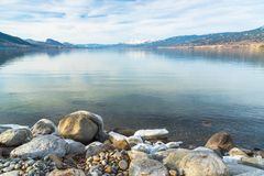 Rocky shoreline in foreground with view of calm lake and snow covered mountains in distance. Rocky shoreline of Okanagan Lake with calm water reflecting sky and Stock Photos