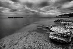 Rocky Shoreline. Landscape featuring a rocky shoreline.  Monochrome image Stock Photos