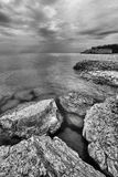 Rocky Shoreline. Landscape featuring a rocky shoreline.  Monochrome image Royalty Free Stock Image
