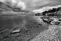 Rocky Shoreline. Landscape featuring a rocky shoreline.  Monochrome image Royalty Free Stock Photo