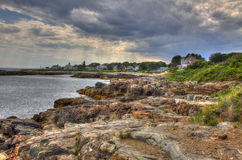 Rocky Shoreline Leading to Houses. A rocky shoreline follows the water with houses at the end Royalty Free Stock Images