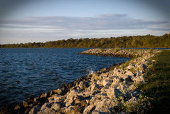 Rocky shoreline of reservoir Royalty Free Stock Images
