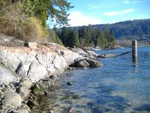 Rocky shoreline. A rocky shoreline in British Columbia where a old piling sits from a missing dock Royalty Free Stock Photo