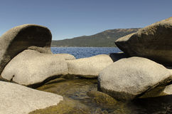 Rocky Shoreline of Scenic Lake Tahoe. A low angle view of the rocky boulders on the shore of  Lake Tahoe that is located in the Sierra Nevada mountains Royalty Free Stock Photos