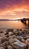 Rocky Shoreline at Sunset on the Water. An image of a vibrant sunset over the mountains from the shore of lake okanagan, bc Stock Image