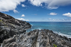 Rocky shoreline of tropical volcanic island Royalty Free Stock Image