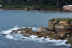 Rocky shores of Coogee Beach, Sydney Australia. Rocky cliffs along the shoreline of Coogee Beach in Sydney, Australia Stock Photo