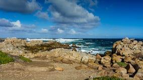 Rocky shores near Pebble beach, Pebble Beach, Monterey Peninsula. USA, California, on a partly cloudy day with blue sky stock photography