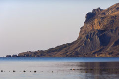 Rocky silhouette of ancient Kara-Dag with reflection in sea.Koktebel. Stock Photography