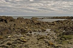 Rocky Skies. The rocky Maine coast with tidepools under and ominous gray sky Stock Photo