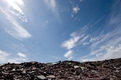 Rocky sky. Rocky hill at a slate quarry framed by a blue expansive sky Royalty Free Stock Photography