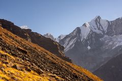 Rocky slope of orange color in contrast with snowcapped mountains in the Himalayas. As seen from Annapurna Base Camp stock photo