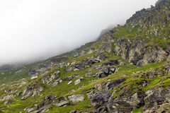Rocky slopes with heavy clouds Royalty Free Stock Images