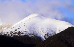 A rocky and snow-capped mountain top Stock Image