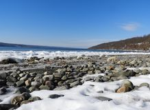 Rocky snow covered shoreline with frozen waves in FLX. Visited just after a sub-zero cold front passed through the area. Cayuga Lake is the longest of central royalty free stock photo