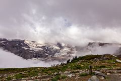 dense white clouds covering snowy mountain stock photos