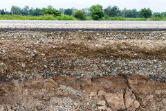Rocky soil under the eroded road. Royalty Free Stock Image
