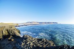 Rocky south coast of Iceland. Atlantic Ocean and rocky coast at Black beach and Dyrholaey natural arch in Vik along southern Iceland coast royalty free stock photo