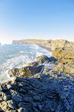 Rocky South coast Iceland. Dyrholaey natural arch in Vik along southern Iceland coast stock photography