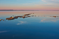 Rocky spit in a calm sea Stock Photos