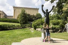 Rocky statue, Philadelphia. Philadelphia, Pennsylvania. Tourist posing with the Rocky statue, a movie memorial close to the 72 Rocky steps before the entrance of stock images