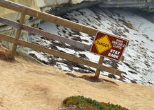 Rocky Steep Cliff. A picture of a sign that says Danger: Sheer Unstable Cliffs, Stay Back in front of some massive cliffs at the beach Stock Images
