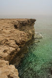 Rocky steep cliff of Cyprus coast to deep blue green Mediterranean sea Stock Photography