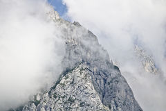 Rocky slope of a mountain partly covered by mist in the Tennen range in the Austrian Alps near the town of Werfen Royalty Free Stock Photo