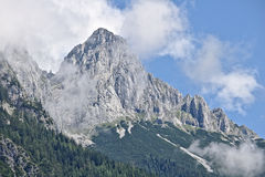 Rocky slope of a mountain partly covered by mist in the Tennen range in the Austrian Alps near the town of Werfen Stock Image