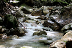 Rocky Stream Time Lapse. A time lapse of a stream passing through a rocky forest Stock Image