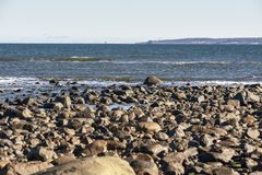 Rocky stretch of beach in Parker River Wildlife Refuge. With distant view of Cape Ann Stock Image