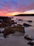 Rocky sunrise. Sunrise in a bay with rocks in the foreground Royalty Free Stock Photo