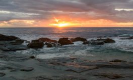 Rocky Sunrise Seascape. Watching the sun come up at Blue Bay, Central Coast, NSW, Australia Stock Image