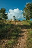 Rocky trail going to lighthouse on top of hill. Covered by green grass and trees, at the highlands of Serra da Estrela. The highest mountain range in stock photography
