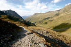 Rocky trail leading to valley surrounded by high mountains in Swiss Alps Royalty Free Stock Image