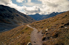 Rocky trail leading to valley surrounded by high mountains in Swiss Alps Stock Images
