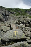 Rocky Trail with yellow arrow. A rocky path to the summit of a mountain with a yellow trail marker pointing upwards Stock Photo