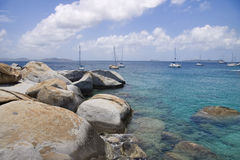 Rocky tropical shoreline. Rocky shoreline of the virgin islands and sailboats anchored in the water Royalty Free Stock Photography