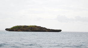 Rocky uninhabited island plateau cliff in ocean with clouds, sky & horizon in background Stock Photos