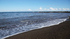 Rocky volcanic beach beach and waves. stock footage