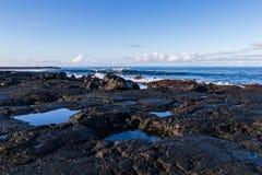 Rocky volcanic shoreline in Hawaii. Low tide; pools of water in rock cavities. Waves, ocean blue sky and clouds in background. Rocky volcanic shoreline at low stock photos