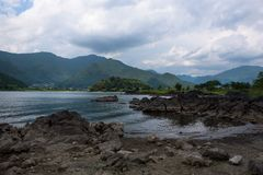 Rocky volcanic shores of the Kawaguchi lake. Rocky volcanic shores as silent reminders of a volcanic eruption in the past of the Kawaguchi lake, Japan Stock Image
