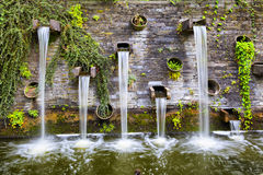 Rocky wall with small waterfalls in Planten un Blomen park Royalty Free Stock Images