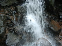 Rocky waterfall. Water cascading down rocky waterfall outdoors Stock Images
