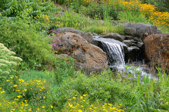 Rocky waterfall. A little waterfall coming out between two large rocks in a garden Stock Photography