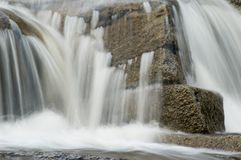 Rocky waterfall. Water cascading down rocky waterfall with slow motion blur effect Stock Images