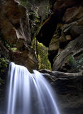 Rocky Waterfall. Water flowing out between two rocks in the Blue Mountains, Australia. Green rain-forest in background Stock Image