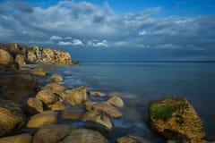 Rocky wild beach, beautiful evening sunlight. stock photos
